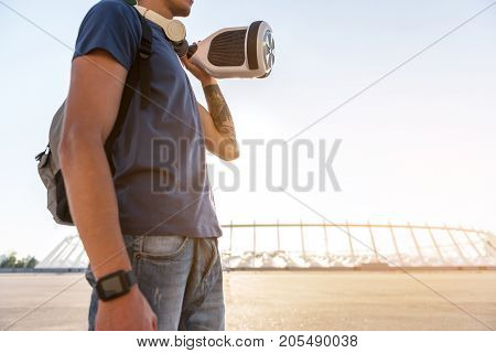 Low angle boy keeping gyroscope while walking in sunny day outdoor. Copy space