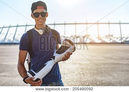 Portrait of friendly scholar holding digital device in arm at street. Technology concept. Copy space