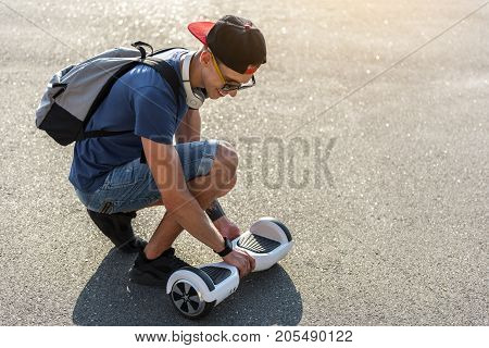 Full length side view cheerful student having fun with hoverboard outdoor. Digital device concept. Copy space