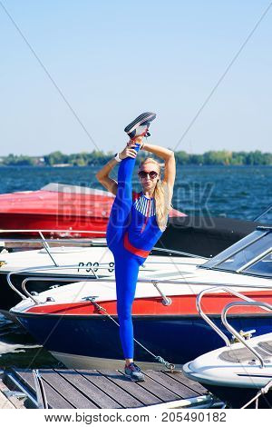 Portrait of a fitness girl on a red yacht background , Twine, raised leg up