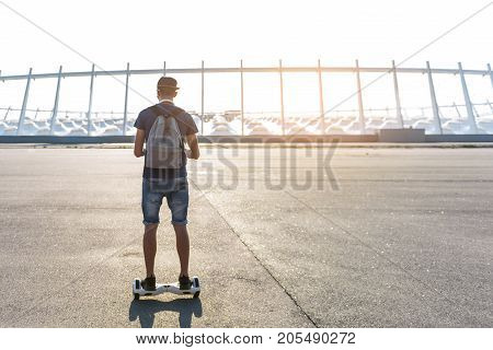 Full length scholar riding on hoverboard at street. He turning back to camera. Copy space