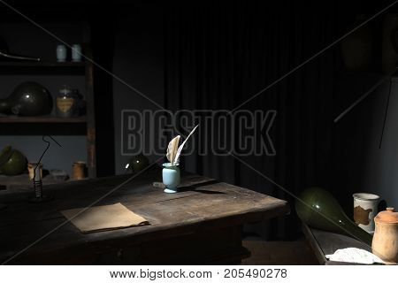 Feather pen on wooden table in dark room closeup photo