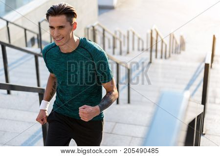Portrait of cheerful man running on stairs at street. Sport concept