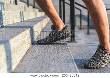 Close up man legs running on stairs at street. Sport concept