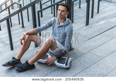 Full length portrait of cheerful man having relax after training outdoor near gyroscooter