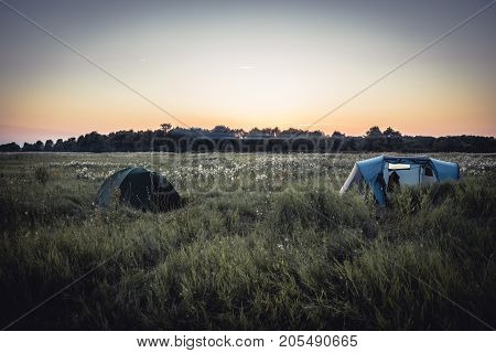 camping site with camping tents on summer rural field and sunset sky during camping holidays