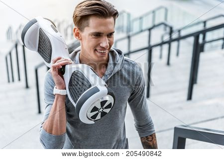 Portrait of happy male athlete holding gyroboard in hand at street