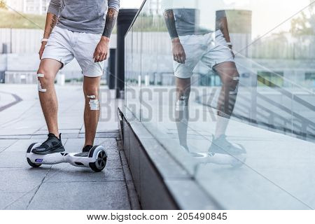 Male legs with adhesive bandage riding on hoverboard near shop-window. He reflecting from it. Digital device concept