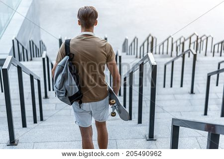 Man going on stairs while holding skate in hand at street. He turning back to camera