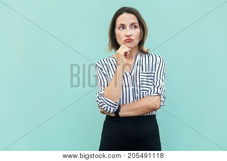 Thoughtful Business Woman Looking Away While Standing Against Light Blue Wall.