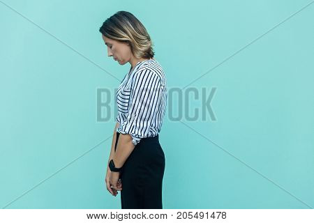 Side View Of Sad Business Woman, Punished Alone At Blue Wall.