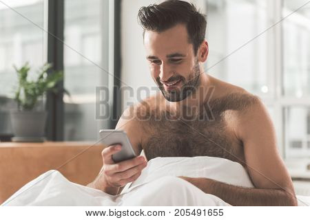 Good news. Portrait of happy young man using smartphone at home. He is sitting on bed after sleeping and smiling