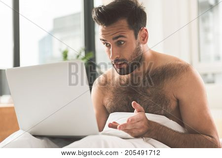 Portrait of shocked young man looking at laptop screen with misunderstanding. He is sitting on bed in the morning