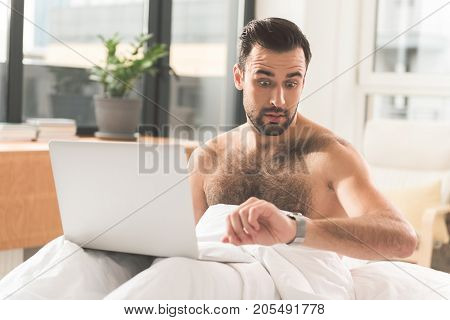 I am short of time. Portrait of nervous young man looking at his watch with shock while sitting on bed in the morning. He is holding laptop on knees
