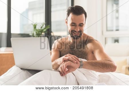 I have plenty of time for rest. Waist up portrait of happy young man looking at his wristwatch with satisfaction. He is sitting on bed with laptop on knees and smiling