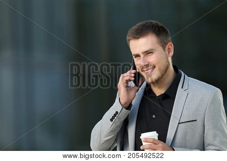Single executive talking in a phone call walking on the street with an office building in the background
