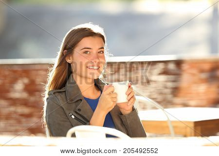 Girl Drinking Coffee And Looking At Camera In A Bar