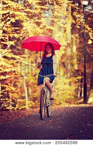 Relax fun leisure outdoor nature fitness concept. Elegant girl cycling. Young ginger woman riding on bike through autumnal park while holding umbrella.