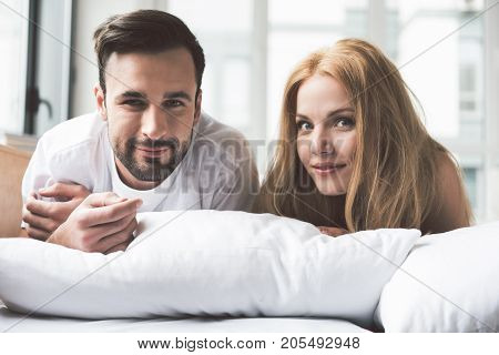 Good morning. Portrait of happy young loving couple lying on bed with relaxation. They are looking at camera and smiling