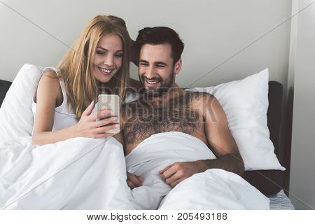 Portrait of joyful young loving couple spending free time in bed together. They are looking at smartphone and laughing