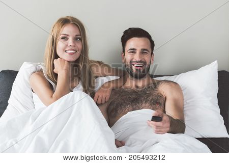 Waist up portrait of cheerful young man and woman watching TV at home together. They are sitting in bed and smiling. Man is holding remote controller