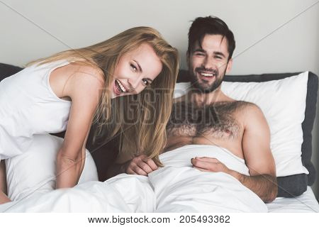 Portrait of happy married couple having fun in bedroom. Girl is holding pillow and looking at camera with excitement. Guy is lying on beddings and laughing
