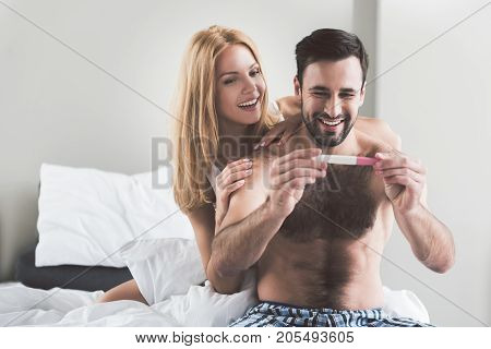 We will be great parents. Portrait of excited married couple looking at pregnancy test stick with happiness. They are hugging and laughing while sitting on bed. Copy space