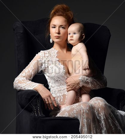 Young mother woman sitting on classic retro chair holding naked her lovely infant child baby girl on dark background