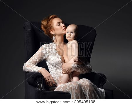 Young mother woman sitting and holding naked her lovely infant child baby girl on dark background
