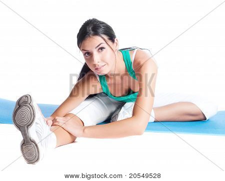 beautiful young brunette woman stretching the muscles of her legs isolated against white background poster