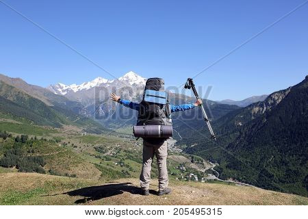 tourist with a large backpack and raised hands standing in front of the mountains