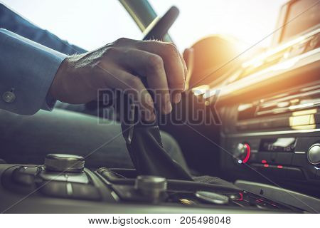Car Driving Concept. Driver Shifting To Drive Mode. Hand on Transmission Stick Closeup