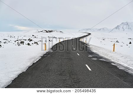 Highway with orange roadside pillars between the snow fields and snow mountains on the background of the cloudy sky in Iceland. Horizontal.