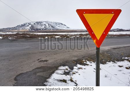 Red-orange road sign on the background of the route, grass field with remains of snow and mountain in Iceland. Sky is cloudy. Horizontal.