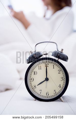 alarm clock standing on bedside table going to ring early morning to wake up woman in bed sleeping in background - early awakening -not getting enough sleep - getting work time concept