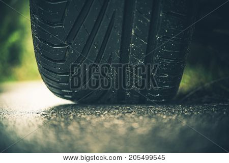 Modern Car Tire on the Road Closeup Photo. Summer Season Pneumatic Tire on a Paved Road.