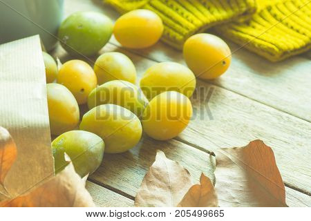 Ripe Yellow Transparent Plums in Brown Craft Paper Bag Scattered on Wood Table Dry Autumn Leaves Knitted Sweater Soft Sunlight Cozy Fall Atmosphere Toned