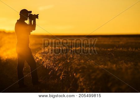 Photographer and the Nature. Men in His 50s Taking Pictures of Scenic Countryside Landscape During Golden Hour.