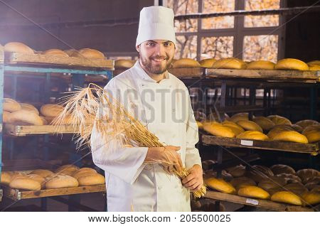 Baker. Bakery. A Young Handsome Worker At A Bakery On A Background Of Shelves With Spikelets Of Whea