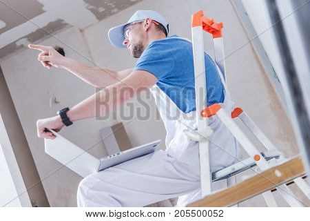 Caucasian Construction Remodeling Worker Explaining His Ideas While Using Laptop Computer with Remodeled Interior Rendered Images.