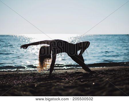 Beautiful young woman practicing morning yoga on sand sea beach. Surya Namaskar - Sun Greetings.