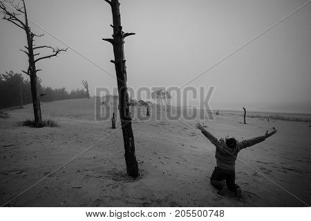 Depressed Man n Has on a Lap Raised Hands Up Against the Background of Dead Trees. Monochrome unfortunate concept