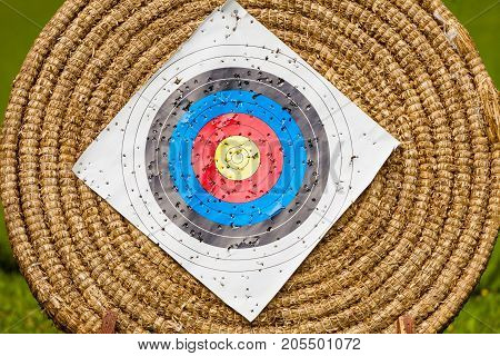 Sport competitions equipment concept. Shooting paper target and bullseye in haystack with many bullet holes