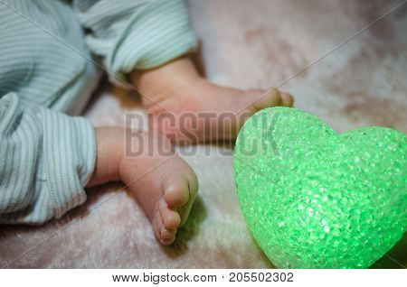 Newborn Baby Feet In Bed Close Up. Happy Family Concept. Beautiful Conceptual Image Of Maternity. Us
