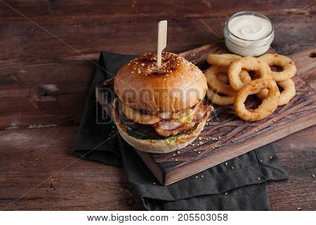 Closeup Of A Tasty Burger With Appetizers Such As Fried Onion Rings With A White Garlic Sauce. Juicy