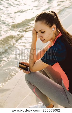 A woman runner holds the phone in her hands and rests after a workout