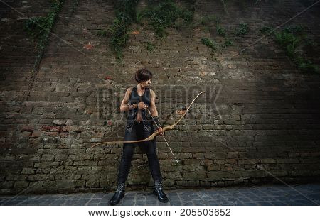 Confident brunette woman warrior prepare for shooting from bow, holding arrow in hand, looking down. Athletic girl in black with short hair using old weapon, posing. Brick wall at old town.