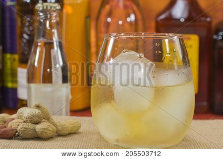 whiskey glass with ice in front of bottles, peanuts on the table and a bottle of soda