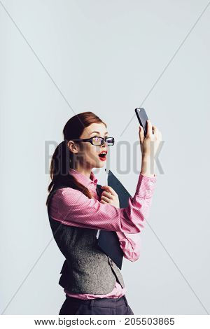Surprised businesswoman girl looks into the phone, wearing a suit. Shock news