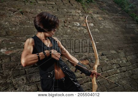 Young athletic brunette wearing in black leather suite, shooting from bow. Female with short hair, bronze sunburn, warrior holding arrow and tacking focus, looking at side. Old times. Brick background.